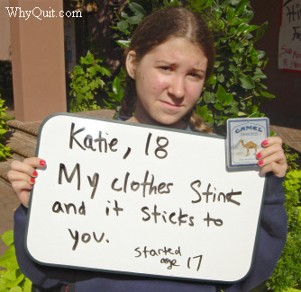 Photo showing 18 year-old Katie, a Camel smoker who became addicted at age 17, holding a sign. Her message reads, 'My clothes stink and it sticks to you.'