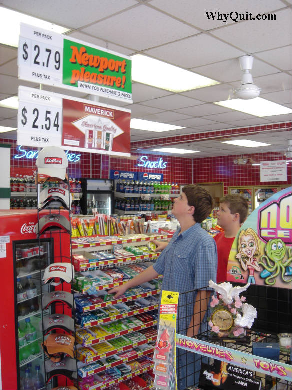 Two boys looking at cigarette advertising signs hanging above a convenience store candy rack