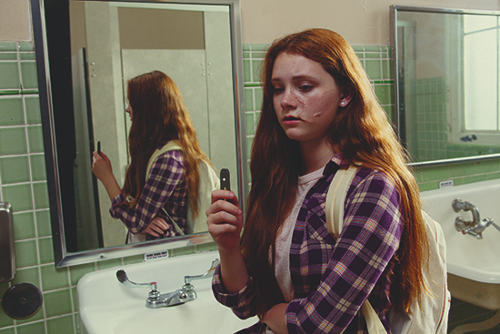FDA photo of a teenage girl holding a Juul while vaping in a school bathroom