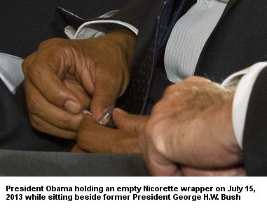 President Obama holding an empty Nicorette wrapper while sitting next to former President George H.W. Bush on July 15, 2013