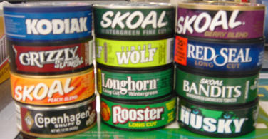Picture of cans of smokeless tobacco including Kodiak, Grizzly straight, Skoal peach blend and fine cut, Wolf, Longhorn wintergreen, Red Seal long cut, Skoal Bandits, Copenhagen snuff, Rooster long cut, and Husky.  Not pictured are Lucky Strike, Bacco, liqurice, pouch snuff, cans, day, General, Onxy, Copenhagen Black, Cougar, Gold, Gold River, Hawken, Beech-Nut, Beech Nut, Chattanooga, Rooster, Redwood, Silver Creek, classic, Red Man, Granger, J.D.S., JDS, J.D.'s Blend, Lancaster, Levi Garrett