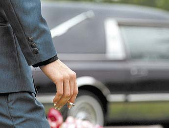 a smoker lights a cigarette after Bryan's June 8 funeral service