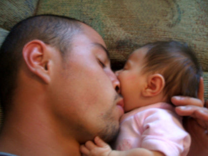 Picture of Quentin Delgado lying with his baby daughter before being diagnosis with kidney cancer.