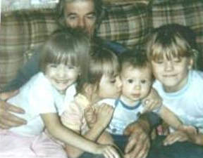 A picture of Holly, her brother and two cousins sharing grandpa's embrace